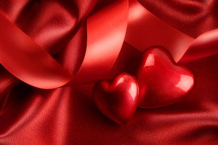 Two red hearts with ribbon on satin background photo