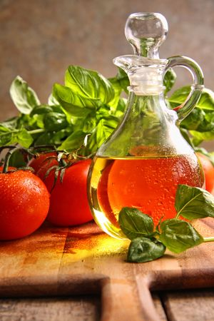 Bottle of olive oil with tomatoes and herbs