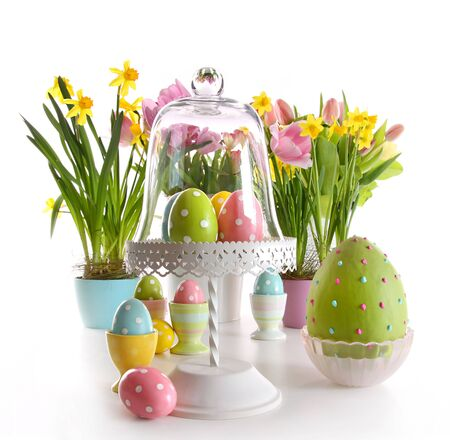 Easter eggs on cake stand with spring flowers on white Stock Photo - 6642292