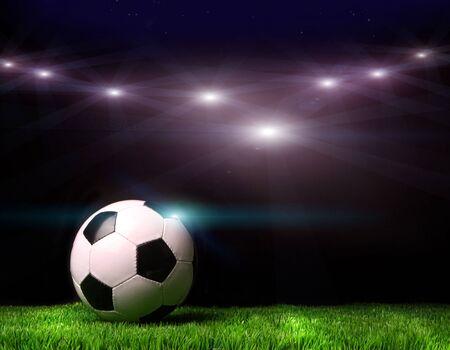 Voetbal op gras tegen zwarte achtergrond