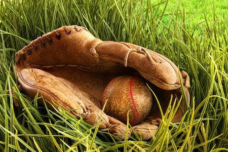 Old leather baseball glove with ball in the grass photo