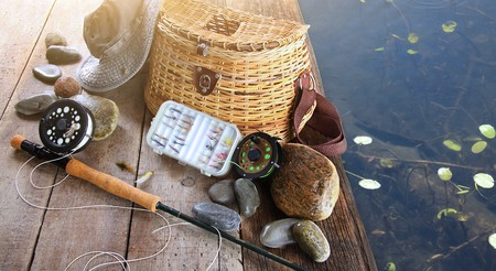 fishing tackle: Close-up of fishing equipment and hat at the lake Stock Photo