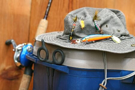 equipment: Fishing tackle box, hat and reel on wood