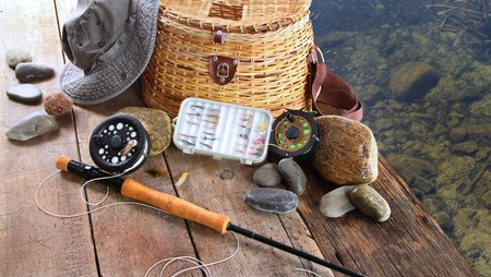 equipment: Fishing lures,reel,and sun hat near lake