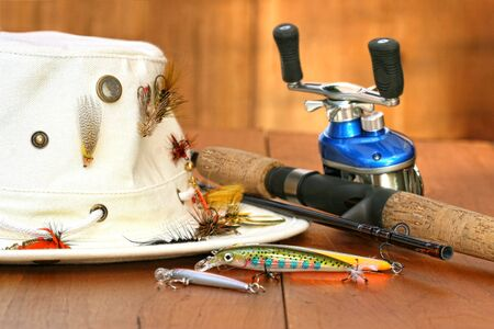 Fishing reel with hat and color lures on wood photo