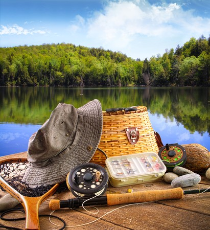 fishing bait: Fly fishing equipment on deck with beautiful view of a lake
