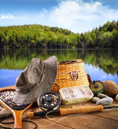 pesca: Volar de equipo de pesca en la cubierta con hermosa vista de un lago
