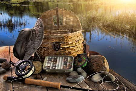 Traditional fly-fishing rod with equipment beside a lake late afternoon