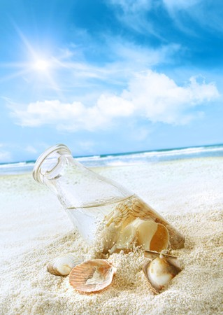 Bottle with seashells in the sand at the beach Stock Photo - 7227062