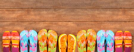 Brightly colored flip-flops on wood deck photo