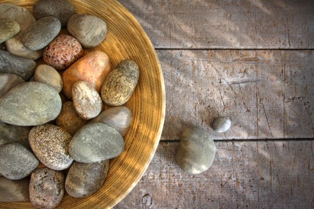 Spa rocks in wooden bowl on rustic wood table photo