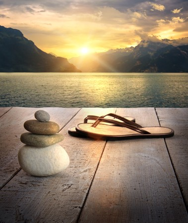 View of sandals and rocks on dock at sunset Stock Photo