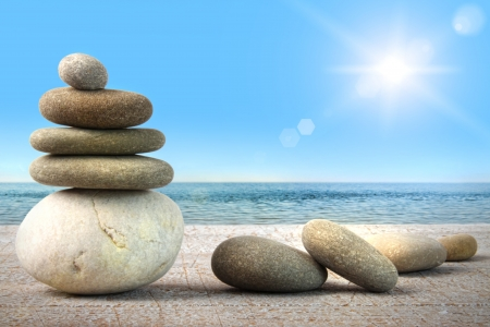 stability: Stack of spa rocks on wood against water and blue sky Stock Photo
