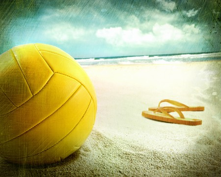 Volleyball in the sand with sandals at the beach photo