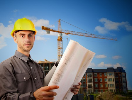 Young architect wearing a protective helmet in front of a building site Stock Photo