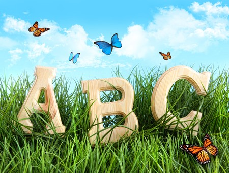 ABC letters in the grass with butterflies Stock Photo