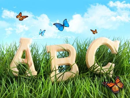 alfabético: ABC letters in the grass with butterflies Banco de Imagens