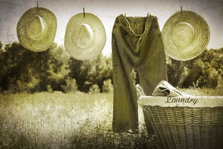 Old grunge photo of jeans and straw hats on clothesline