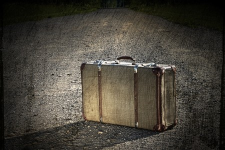 maleta: Maleta vieja izquierda por un camino de tierra