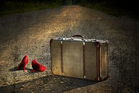 maleta: Maleta antigua con zapatos rojos de izquierda por un camino de tierra