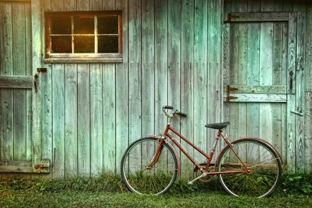 fiets: Oude fiets leunend tegen grungy schuur