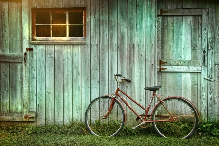 bicicleta retro: Vieja bicicleta apoy�ndose contra grungy granero