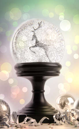 Snow globe with ornaments against a colored background photo