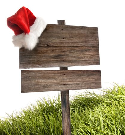 Weathered wooden sign with Santa hat and grass on white Stock Photo - 8163277