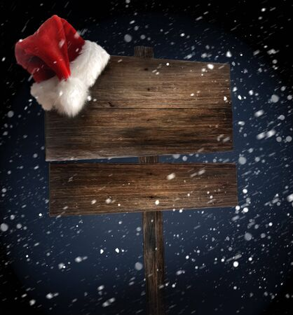 Weathered wooden sign with Santa hat in snow