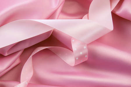 Pink satin silk  background with colored ribbons photo