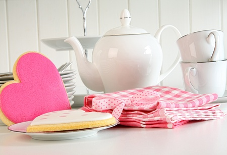 Heart-shape valentine cookies with teapot and cups on kitchen counter   Stock Photo