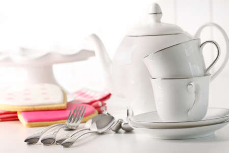 Porcelain teapot with cups and valentine cookies in background photo
