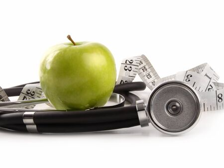 Green apple and measuring tape with stethoscope on white background photo