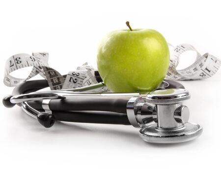 Green apple with stethoscope against white background photo