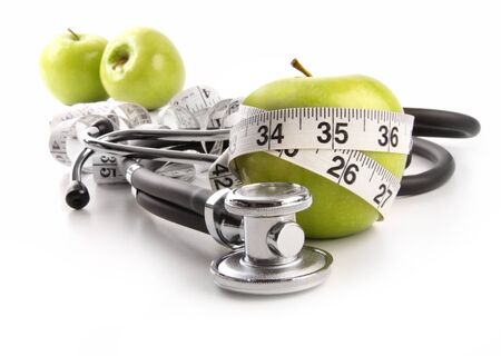 Green apples with stethoscope against white background photo