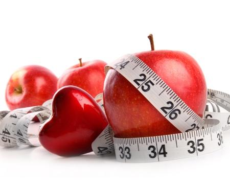 cinta metrica: Manzanas rojas, el coraz�n y la medici�n de la cinta sobre fondo blanco Foto de archivo