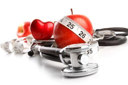 stetoscoop: Stethoscoop met rode appels op een witte achtergrond