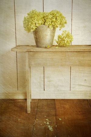 Hydrangea flowers in bucket on rustic bench with age vintage look