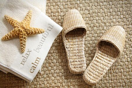 Spa slippers on seagrass carpet with towels and starfish photo
