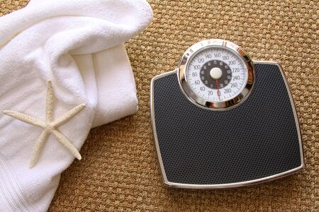 Weight scale with white towel on seagrass carpet photo