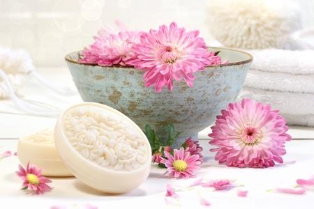 Escena de spa con flores de Crisantemo Rosa en agua y jabón