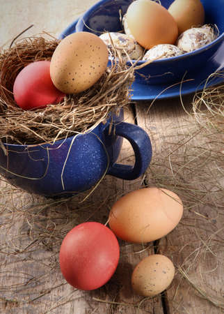 Colored easter eggs in blue enamel cup with straw photo