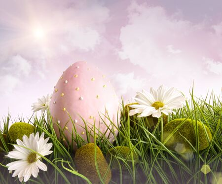 Large pink easter with flowers in tall grass with sky  photo