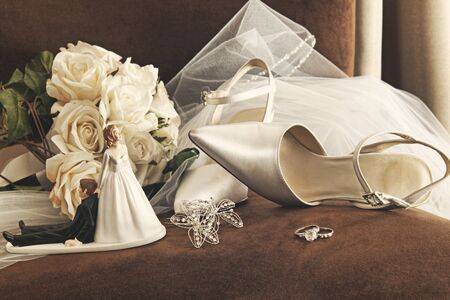 argent: Bouquet of white roses, rings and satin wedding shoes on chair