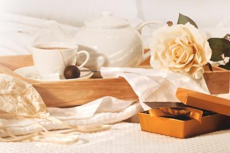 afternoon: Descanso en la cama con t� y deliciosos Bombones Foto de archivo