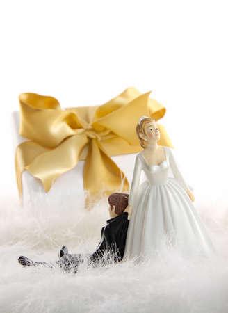 Wedding cake figures with gold ribbon gift on white photo