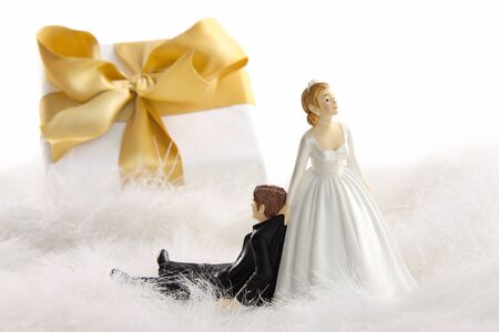 Wedding cake figurines with gold ribbon gift on white Stock Photo