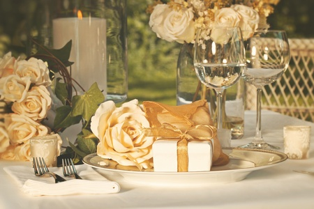 Gold wedding party favors on plate at reception photo