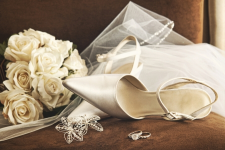 bridal veil: Wedding shoes with bouquet of white roses and ring on chair Stock Photo