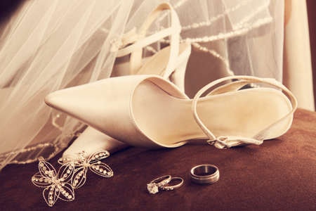 Wedding shoes with veil and rings on velvet chair photo